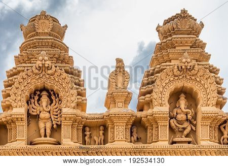 Nanjangud India - October 26 2013: Double Niche in beige elaborately decorated sandstone at Srikanteshwara Temple showing both statue of Lord Ganesha one standing one dancing.