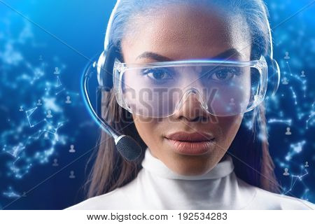 Portrait of confident female operator talking with client through internet technology. She is wearing eyeglass of future with microphone. Graphic design