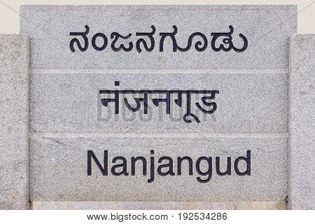 Nanjangud India - October 26 2013: Gray stone sign at entrance of the city showing its name in Hindi Kannada and English languages.