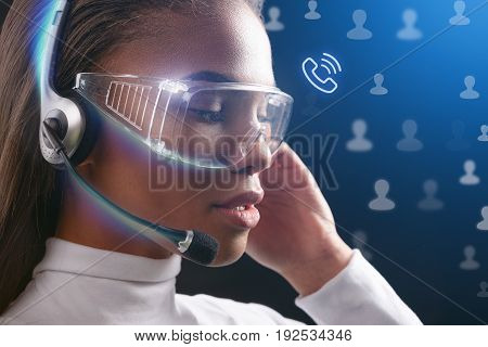 Profile of serious female call center worker speaking with people by futuristic communication network. She is touching headphones while wearing transparent eyewear