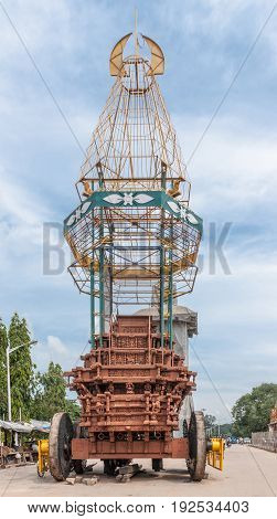Nanjangud India - October 26 2013: Huge wooden holy procession chariot on side of Srikanteshwara Temple against blue cloudy sky. Street scenery with merchant booths Heavy wood carved foot on wheels scaffold buildup.