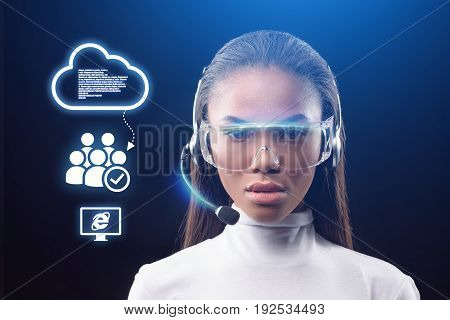 Future network communication. Portrait of calm young woman wearing headset and eyeglasses. She is looking at digital touch screen with cloud sign