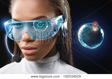 I can find you anywhere. Confident young woman is wearing futuristic glasses with new scrutiny technology. Exact human location is on the globe