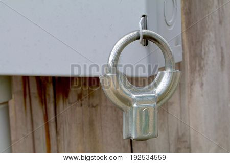 Silver clamp style lock on an electrical box