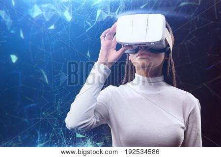Excited young woman is using virtual reality device for internet connection