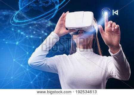 Confident african girl is watching vr headset while touching abstract display button. Social network hologram on background