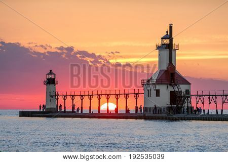 On the Summer Solstice the sun sets on Lake Michigan between the Inner and Outer North Pier Lighthouses at St. Joseph Michigan.