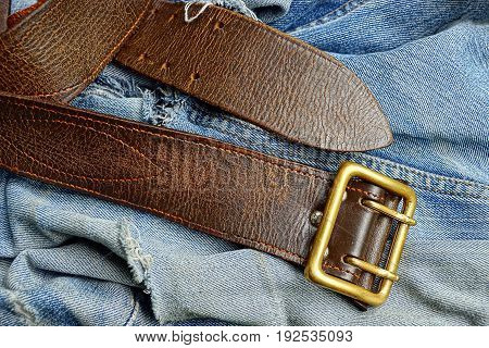 Brown belt with a copper buckle and torn jeans