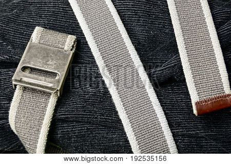 The gray belt is wound on black velveteen trousers