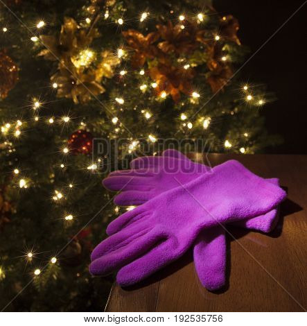 Christmas tree with lights in the background of a pair of pink gloves