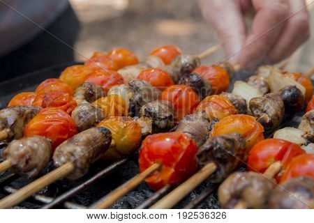 Chicken Hearts With Tomato And Onion Cooking On Hot Grill