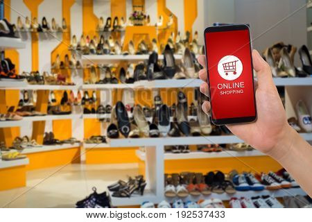 human hand hold smartphone tablet cell phone with blue screen and online shopping button on blurry shelf shoe shop background.
