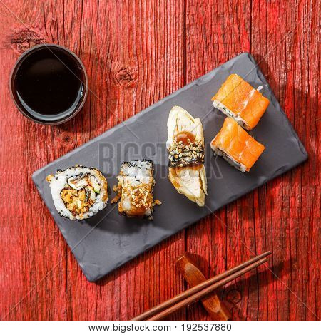 Rolls served on black board at red wooden table