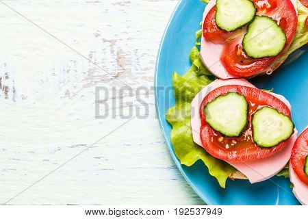 Bruschetta with salad, sausage, tomato and cucumber on white wooden table