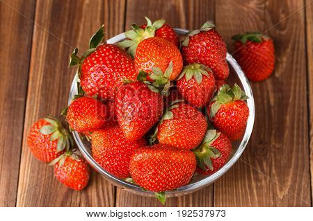 Picture of fresh ripe strawberry in cup on wooden table