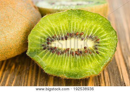 Two Kiwi Fruits sit on the cutting board on cut in half