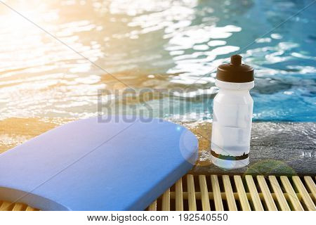 Kick board and water bottle on swimming pool