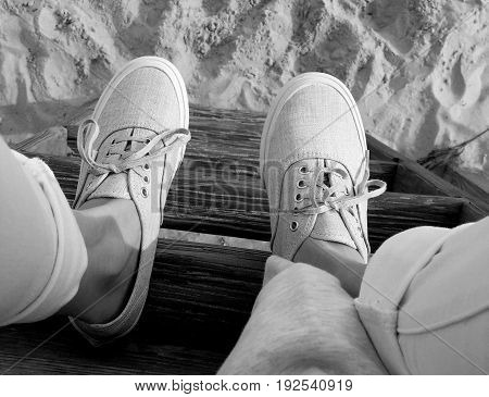 black and white photo of shoes, sneakers, on a ladder at the beach