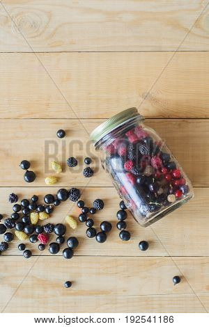 Red white black currant red and black raspberries white strawberries in glass jar and sprinkle on wooden table as canned food