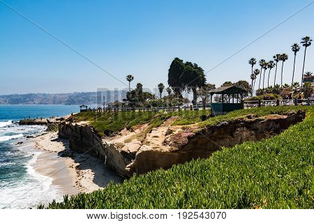 LA JOLLA, CALIFORNIA - JUNE 16, 2017:  La Jolla Cove in San Diego, California, with two observation points, palm trees, and people enjoying the view.