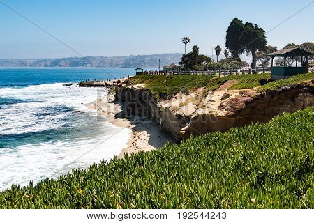 LA JOLLA, CALIFORNIA - JUNE 16, 2017:  Ice plants on a cliffside at La Jolla Cove in San Diego, California, with two observation points and people enjoying the view.