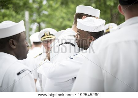 Participating U.S. Navy sailors hug and congratulate each other after the re-enlistment and promotion ceremony at the National September 11 Memorial site. Fleet Week, NEW YORK MAY 26 2017
