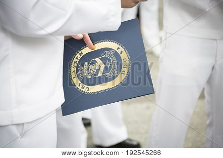 U.S. Navy sailor holds ceremonial folder with insignia of USS Lassen (DDG-82) after the re-enlistment and promotion ceremony at the National September 11 Memorial site. Fleet Week NEW YORK MAY 26 2017