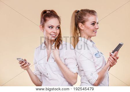 Technology communication and friendship concept. Two teen girls casual style using mobile phone reading message standing back to back