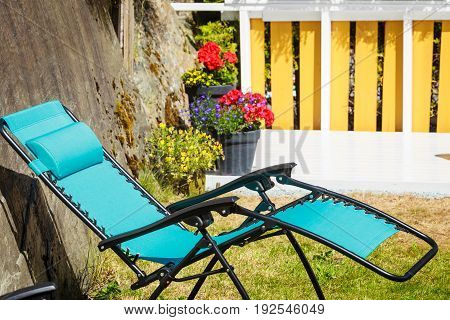 Recreation and relaxation objects concept. Blue modern sunbed deck chair in garden.