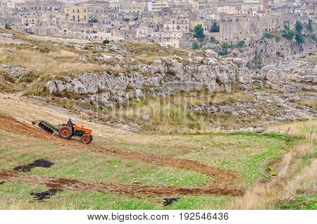 A farmer is ploughing his field just a stone's throw away from Sasso Caveoso the startling cave town - Matera Basilicata Italy, 26 October 2011