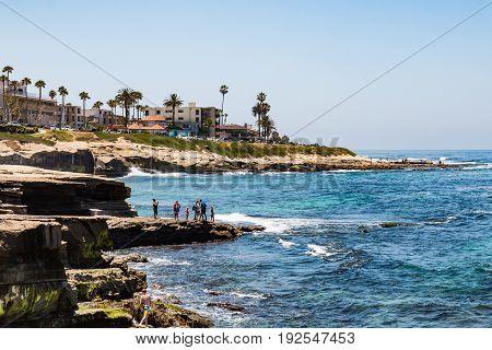 LA JOLLA, CALIFORNIA - JUNE 16, 2017:  People enjoying the ocean view from natural sandstone rock formations at La Jolla Cove.
