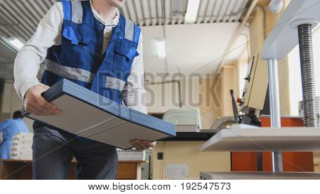 Printing worker carries a stack of paper, in a printing factory