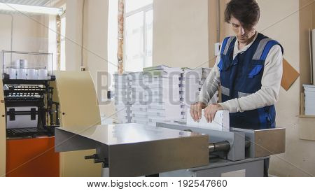 The print operator checks the quality of the finished product, in a printing factory