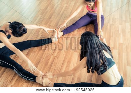 Women Practicing Yoga Pose In Fitness Gym Class