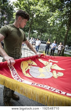Military Freedom Run: U.S. Marine Corps personnel folds a Marine Corps Flag carried during the Freedom Run to the National September 11 Memorial site. Fleet Week, NEW YORK MAY 26 2017