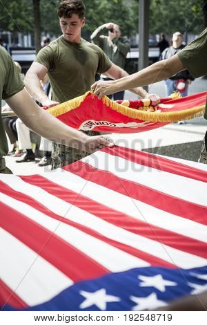 Military Freedom Run: U.S. Marine Corps personnel fold the Marine Corps Flag and American Flag carried during the Freedom Run to the National September 11 Memorial site Fleet Week NEW YORK MAY 26 2017