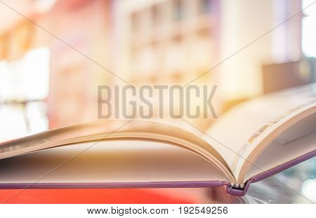 open book light on glass desk in color library room with blurred focus shelf background education back school and learning concept