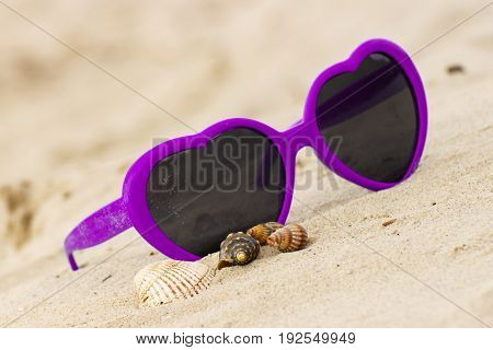 Purple Sunglasses Shaped Heart With Shells On Sand At Beach, Vacation Concept