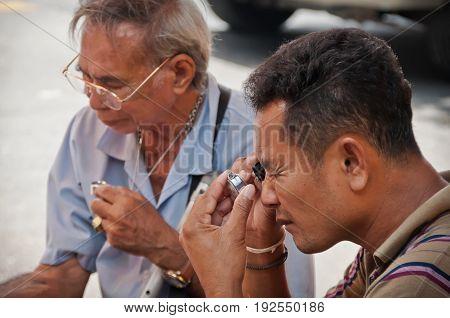 BANGKOK THAILAND-JUNE 19: Unidentified Thai Buddhism inspects on buddha amulets at amulet market on June 19 2011 in BangkokThailand.
