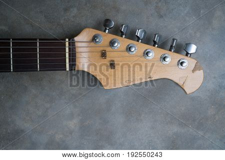 detail of vintage electric guitar headstock on the concrete background.