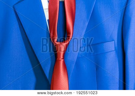Part of the blue man's suit and red tie hanging on the hanger close up
