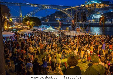 PORTO, PORTUGAL - JUN 24, 2017: Participants Sao Joao Festival (birth of St.John the Baptist) Very popular holiday is celebrated 23-24 June at midnight, next to the Douro River and Dom Luis I bridge.