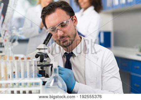 Scientist Looking Through Microscope In Laboratory, Male Researcher Doing Research Experiments In Modern Lab