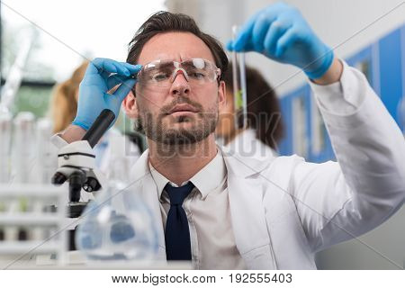 Scientist Analyzing Examining Sample Of Plant In Test Tube Workin In Genetics Laboratory, Man Researcher Study Experiment Result