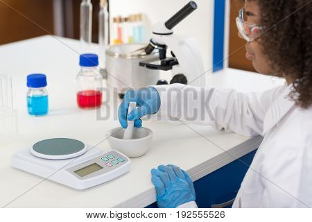 Female Scientist Using Mortar Working In Laboratory Making Chemicals Powder For Experiment, Researcher Mix Race In Modern Lab