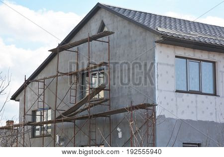 Painting Plastering Stucco and insulate Exterior House Wall. Facade Thermal Insulation and Painting Wall Repair Works During Exterior Renovations. Wall Insulation and Repair. Plastering Wall.