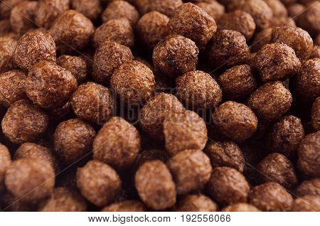 Chocolate balls corn flakes closeup background. Cereals texture.