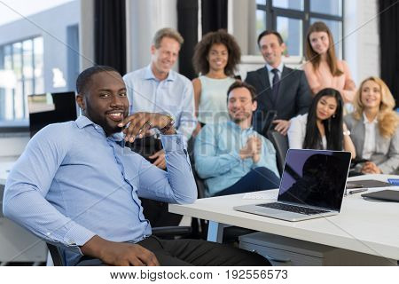 African American Businessman Leading Meeting In Creative Office, Boss Using Laptop Computer In Foreground Over Business People Team Sitting At Desk, Discussing Ideas