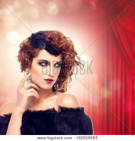 Beautiful retro style young woman with dark make-up and feathers on head over red curtain background. bokeh effect. Copy space. square composition