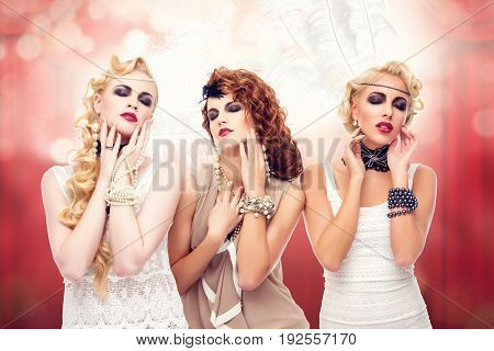 Three beautiful retro style young women with dark make-up and feathers on head on red curtain background. bokeh effect. Copy space.